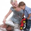 A mother showing a book to her little boy playing with a car - Stock Photo