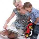 en mamma som visar en bok till sin lilla pojke som leker med en bil — Stockfoto