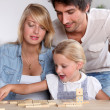 Happy couple playing dominos with daughter — Stock Photo