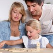 Happy couple playing dominos with daughter — Foto de Stock
