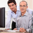 Man helping granddad with computer — Stock Photo