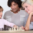 Parents and daughter playing chess — Stock Photo #10501838