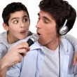 Father and son listening music and singing — Stock Photo
