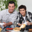 Father and son playing video games and eating junk-food — Stock Photo #10502195