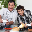 Man and boy playing to video games - Stock Photo