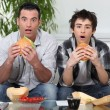 Brothers staring in amazement while eating a hamburger — Stock Photo