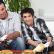 Father and son playing video games whilst eating fast-food — Stock Photo