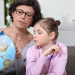 Grandmother with granddaughter looking at globe — Stock Photo
