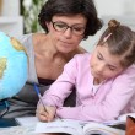 Frau, die ein Kind bei ihr Geographie-Hausaufgaben helfen — Stockfoto