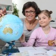 Mother helping daughter with geography homework — Stock Photo
