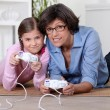 Stock Photo: Mother and daughter playing video games