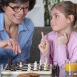 Mother and young daughter playing chess together - Stock Photo