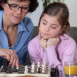 Girl and her grandmother playing chess — Stock Photo