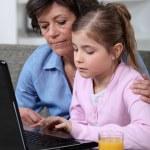 barnet och hennes mormor som använder en bärbar dator — Stockfoto