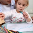 Man with little girl colouring — Stock Photo