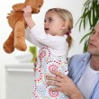 Stock Photo: Little girl playing with teddy bear