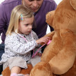Little girl playing with teddy bear — Stok fotoğraf