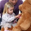 Little girl playing with teddy bear — Stockfoto