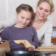 Mother and daughter making crepes together — Stock Photo