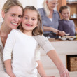 Young girl baking with her mother — Stock Photo