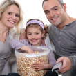 Family eating popcorn in front of television — Stock Photo