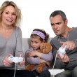 Man and woman playing to video games with little girl pouting — Stock Photo