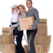 Young family with moving boxes — Stock Photo