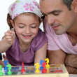 Little girl playing to a board game with man — Stock Photo #10503233
