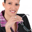 Businesswoman holding a pair of glasses — Stock Photo