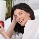 femme au lit avec apple en main — Photo
