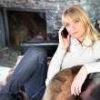 Blond woman sat making call on sofa — Stock Photo