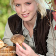 Blonde girl with mushrooms in hand — Stock Photo #10508709