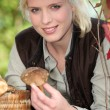Blonde girl with mushrooms in hand - Stock Photo