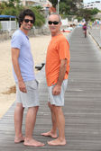Grandfather and grandson walking along the beach — Stock Photo