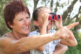 Grandmother with granddaughter and binoculars — Stock Photo