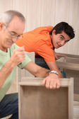 Grandfather with grandson assembling furniture — Stock Photo