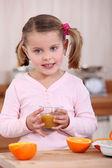 Girl drinking orange juice — Stock Photo
