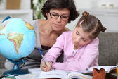 Woman helping a child with her geography homework — Stock Photo