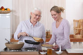 Mother and daughter cooking crepes — Stock Photo