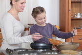 Woman teaching her daughter how to make crepes — Stock Photo