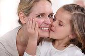 Little girl kissing woman — Stock Photo