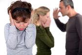Chica joven tratando de bloquear el sonido de sus padres discutiendo — Foto de Stock