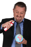 Businessman spraying a globe with an aerosol — Stock Photo