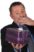 Portrait of a man surprised in front of a gift package — Stock Photo