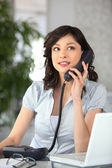 Receptionist answering the telephone — Stock Photo