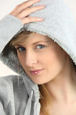 Blue-eyed blonde wearing with hand on hood — Stock Photo