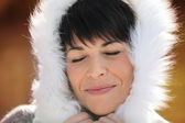 Woman wearing coat with fluffy hood — Stock Photo