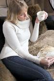 Woman relaxing on sofa with mug of coffee — Stock Photo
