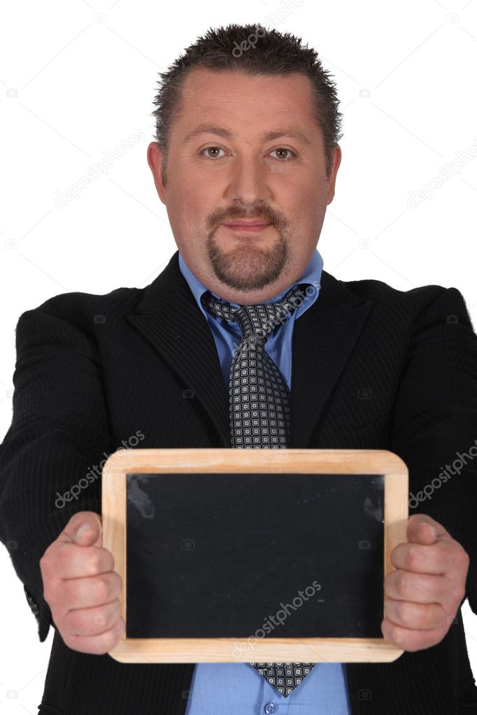 Businessman holding a blackboard left blank for your message — Stock Photo #10504311