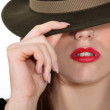 Shy women shielding face with hat — Stock Photo